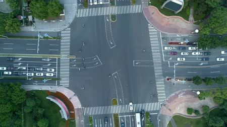 csomópont : Accelerated aerial drone rotating shot of crossroad in the city, cars and buses driving by avenue. at sunset Stock mozgókép