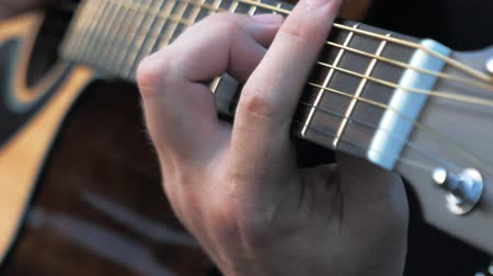 akord : Close-up side angle shot of fingers playing a guitar. Musician clamps the chords on the guitar frets.