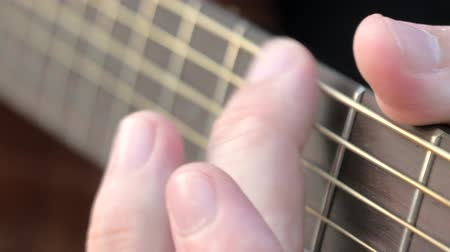 hmatník : Close-up side angle shot of fingers playing a guitar. Musician clamps the chords on the guitar frets.