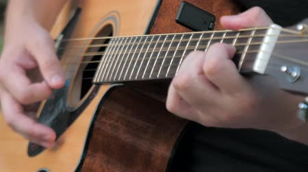 akusztikus : Close up of a young man playing acoustic guitar outside. Hands of a man playing the brass strings of a guitar. Musician clamps the chords on the guitar frets.