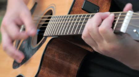 bassê : Close up of a young man playing acoustic guitar outside. Hands of a man playing the brass strings of a guitar. Musician clamps the chords on the guitar frets.