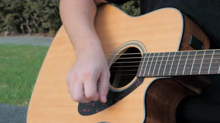 menores : Close up of a young man playing acoustic guitar outside. Hands of a man playing the brass strings of a guitar. Musician playing an acoustic guitar using strumming technique. Archivo de Video