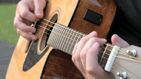 menores : Close up of a young man playing acoustic guitar outside. Hands of a man playing the brass strings of a guitar. Musician clamps the chords on the guitar frets.