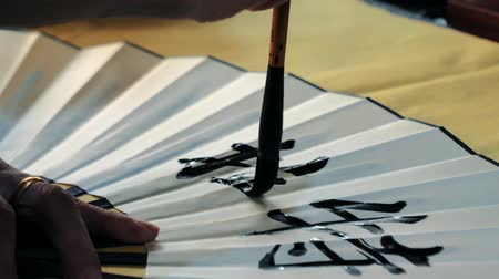hieroglifa : Calligrapher writes hieroglyphs on paper fan. Stock mozgókép