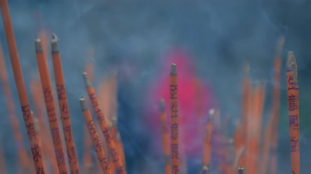 babona : Incense sticks are burning slowly in the burner of a chinese temple. Slow motion shot.