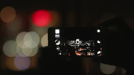 atirar : Man capturing video with his camera in the night, night lights bokeh
