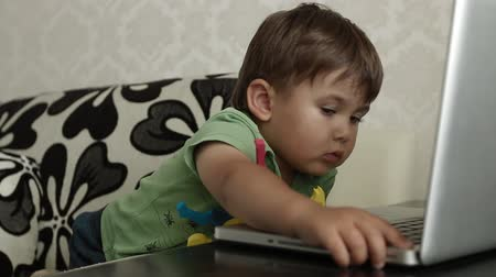 yawning : Baby boy watching laptop Stock Footage