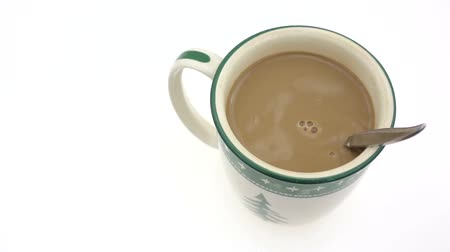 lét : Video of a mug of coffee with cream being stirred on a white background.