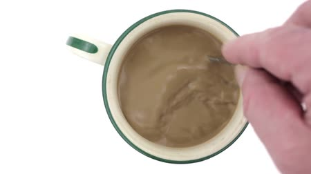 feketés csésze : Top view video of a cup of coffee with creamer being stirred on a white background.