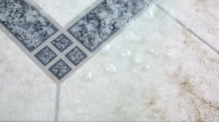 dlaždice : Video of a liquid cleaner being sprayed onto a dirty floor tile.