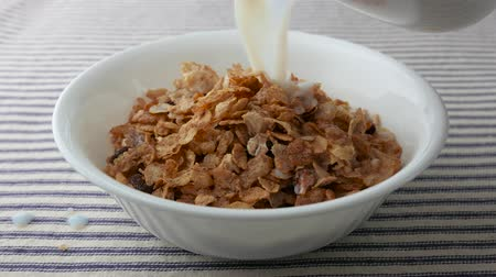yulaf ezmesi : A bowl of pecans, raisins and dates breakfast cereal having skim milk sloppily poured onto the cereal upon a striped table cloth.