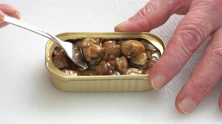çatallar : A working mans fingers holding a tin of smoked scallops while eating.