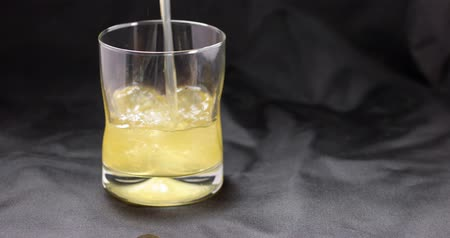 pouring : Video of pouring a full glass of coconut water on a black cloth background.