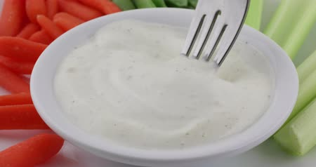 горох : Generously coating a peeled carrot in ranch dressing with a fork with the bowl surrounded by more vegetables.