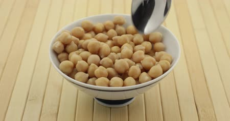 bezelye : A bowl filled with organic garbanzo beans with a spoon trying to scoop chickpeas with a pause each time a bean spills from the bowl. Stok Video