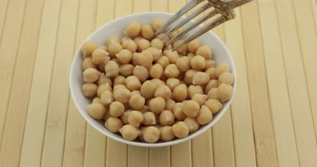 bezelye : A bowl filled with organic garbanzo beans with a fork trying to skewer a chickpea with one bean flying out of the bowl.