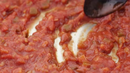 pimentas : Close video of chunky thick spaghetti sauce being slowly stirred in a stainless steel skillet with a black spoon.
