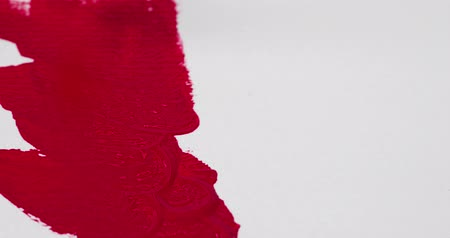 applying : Close video of white heavyweight artist paper being painted with deep red crimson acrylic paint.