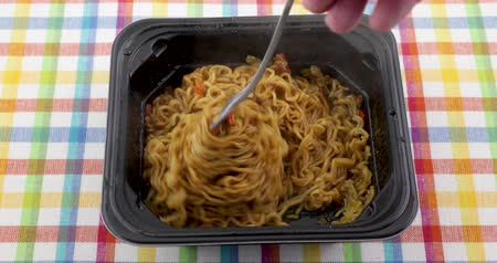 çatallar : Video of eating beef flavored ramen noodles with a fork in a black microwavable tray atop a colorful place mat.