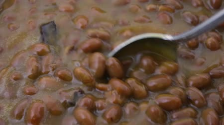 światłowód : Close video of bacon and onion flavored baked beans being slowly stirred with a spoon then taking one spoonful.