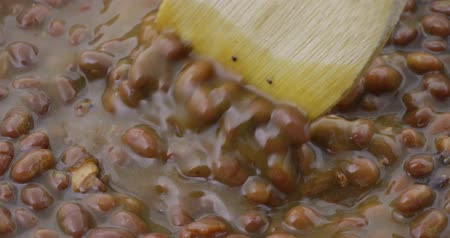 rim : Close video of bacon and onion flavored baked beans being stirred while heating with a wood spoon.