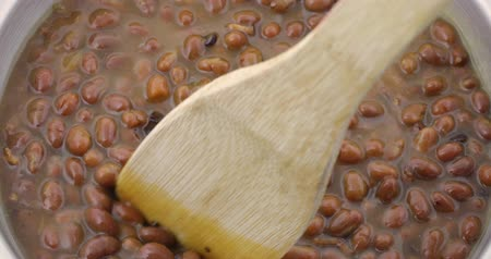 консервированный : Bacon and onion flavored baked beans being stirred while heating in a stainless steel pan with a wood spoon. Стоковые видеозаписи