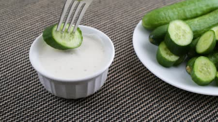 Video of a plate of whole and sliced bite size cucumbers next to a bowl of ranch dressing with one cucumber slice being slowly picked up and dipped into the dressing.