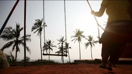 houpavý : Woman swinging on the swings in silhouette near the ocean and palm trees in Kovalam, Kerala, India Dostupné videozáznamy