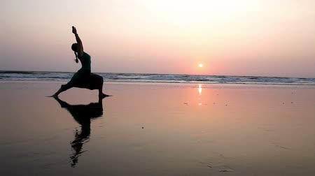 Woman doing Yoga complex on the beach at sunset in India