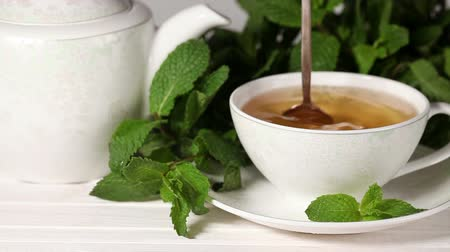 copinho : Woman stir with a spoon into the Cup tea with mint Stock Footage