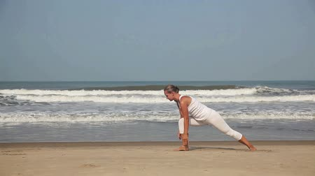goa beach : Woman doing yoga in white costume on the beach near the ocean in Goa, India Stock Footage