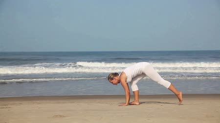 posição : Woman doing yoga in white costume on the beach near the ocean in Goa, India Vídeos