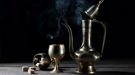 Metal pot and cup with moroccan tea and smoke at black background with brown shugar nearby