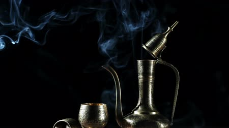herbal : Metal pot and cup with moroccan tea and smoke at black background with brown shugar nearby