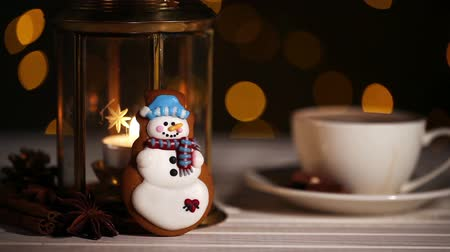 kardan adam : Snowman Christmas cookie near lantern with candle and cup of coffe with blinking lights bokeh on background