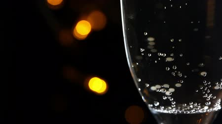 Glass of champagne with bubbles  at yellow light bokeh on black background