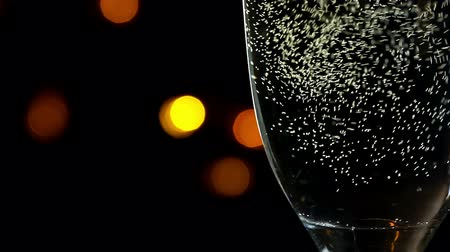 пузыри : Glass of champagne with bubbles  at yellow light bokeh on black background