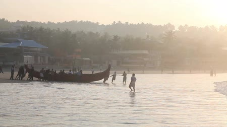 Indian fishermen in silhouette with fishing nets near the boat on the beach in the morning at lighthouse background in Kovalam, Kerala, India
