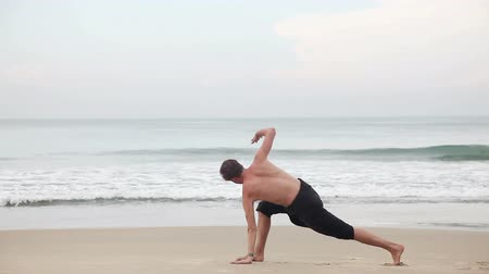 Man doing Yoga on the beach near the ocean in India