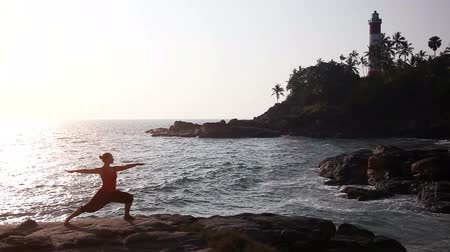 Young healthy woman in silhouette practicing yoga on the beach at sunset near lighthouse in India Wideo