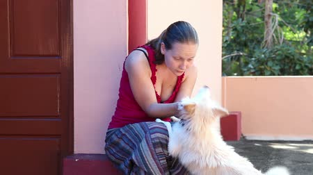 Beautiful young woman playing with dog near her house