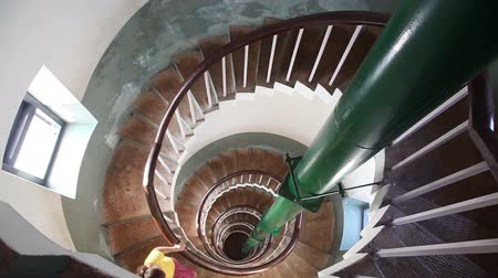 Woman going down by spiral stairs inside of lighthouse in Kovalam, Kerala, India Wideo