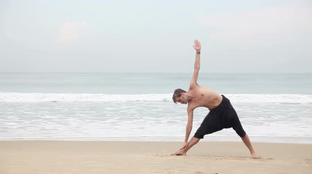 Man doing Yoga asana on the beach near the ocean in India Wideo