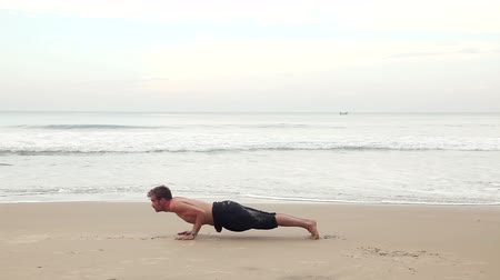 Man doing Yoga complex on the beach near the ocean in India Wideo