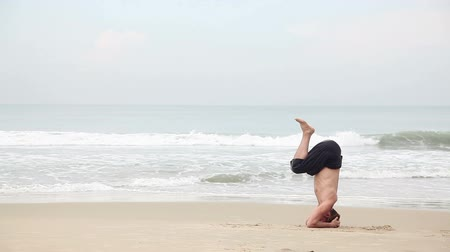 Man doing Yoga headstand on the beach near the ocean in India