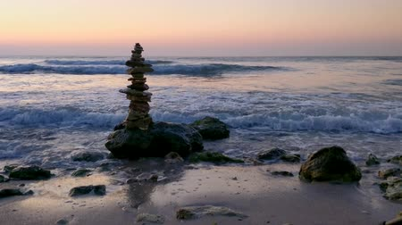 Zen stones in the morning day at the seashore with waves Stock mozgókép