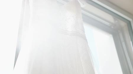 decisões : A white wedding dress hanged on the hanger. Buying a wedding dress. Stock Footage