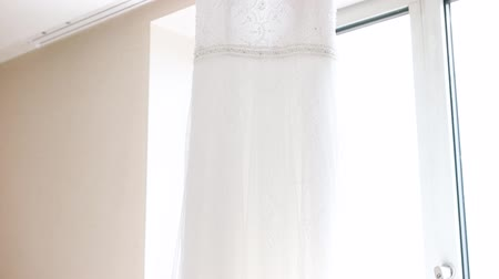seçme : A white wedding dress hanged on the hanger. Buying a wedding dress. Stok Video