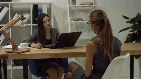 espetáculos : Charming female headhunter interviewing attractive female job applicant at desk in modern office. Skillful female hr manager communicating and reviewing resume of lovely woman in office enviroment Stock Footage