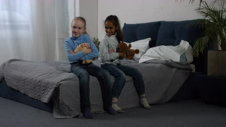 reconcile : Multiracial preteen girls with plush toys in hands sitting on the bed with pouting expression after argument at home. Two multi ethnic elementary best friends reconciling after argument and playing Stock Footage